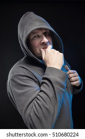 Emotional actor brutal man with a beard in a hood on a black background