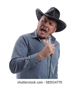 emotional actor man in a gray shirt and black hat with microphone in hands sings on a white background in studio