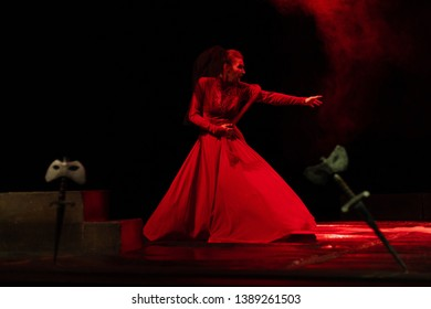 Emotional Actress in an old red dress dancing and playing a role on the stage of the theater in the red light