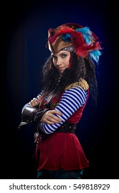 emotional actress woman in a pirate costume with a gun on a blue-black background