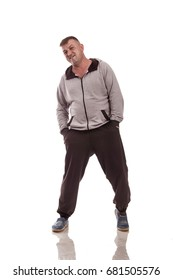 Emotional adult male actor in sports suit posing against white background in studio