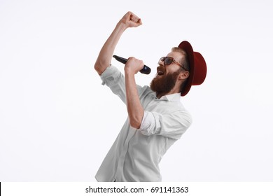 Emotional adult male entertainer, actor or pop-singer wearing white shirt, stylish hat and sunglasses, holding wireless microphone, speaking or singing in studio. Show, entertainment and performance