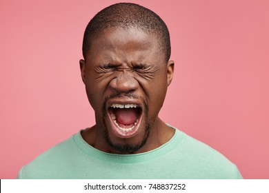 Emotional African American male closes eyes in despair, opens mouth, yells loudly, being scared of horror film. Frightened dark skinned man afraid of something, isolated over pink background