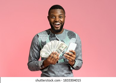 Emotional african american young man holding bunch of cash and mobile phone over pink studio background, copy space. Rich black guy in traditional costume won prize, gambling online, using smartphone