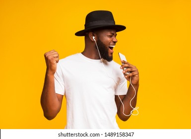 Emotional african guy in black hat singing into smartphone like microphone and listening to music via earphones, yellow background with free space