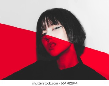 Emotional asian girl peeking over red plastic filter at the camera, dangerous emotional expression.
