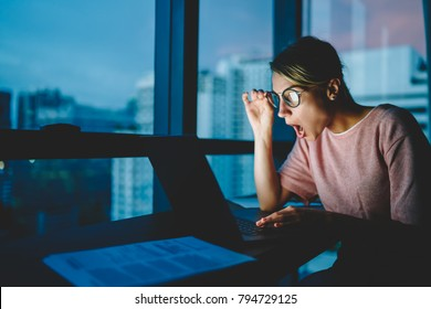 Emotional astonished web designer in eyeglasses shocked from last trendy news watching video in network sitting in evening at home. Female shocked with read information in internet receiving news