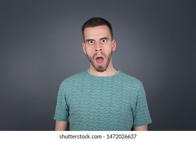 Emotional attractive male with opened mouth expresses great surprisment and frighteness, poses against white concrete background, stares at camera. Unexpected shocking news and human reaction.