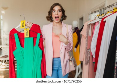 emotional attractive woman holding colorful dresses on hanger in clothing store, shopaholic, crazy exited emotion, happy face, spring summer fashion trend, choosing apparel, surprised discount sale