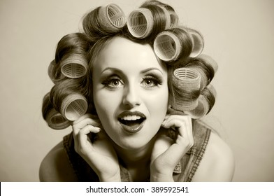 Emotional beautiful girl with curlers on her head vintage background