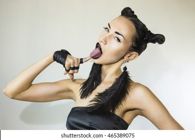 Emotional Beautiful Sexy Stylish Woman licking with tongue. Cheeky Youth - Club Trendy look. Stylish Fashion Accessory (Feather earrings, gloves), Creative Hairstyle, Make-up. Emotional cheerful Girl