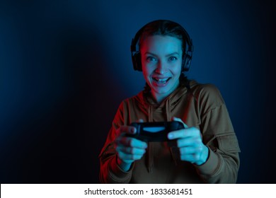 Emotional beautiful woman playing online video game with headphone and joystick on dark blue background. Gaming concept. Funny entertainment.