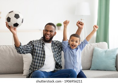 Emotional Black Father And Son Watching Sports On Television Shaking Fists Celebrating Victory Of Favorite Soccer Team At Home. Family Leisure And Entertainment. Sport TV Programming