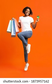 Emotional black lady shopaholic holding credit card and colorful bags with purchases, jumping up on orange studio background. Unlimited shopping with credit card or loan for shopping