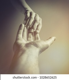 Emotional, black and white photo of two hands at the moment of farewell. The concept of breaking relations.