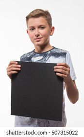 Emotional blond boy in a white shirt with a gray sheet of paper for notes on a white background