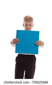 Emotional blond boy in white shirt is holding a blue sheet of paper for notes, posing against white background