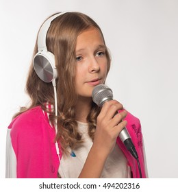 Emotional blonde girl in a pink jacket with a microphone and headphones.