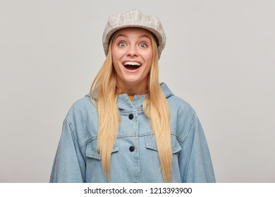 Emotional blonde young woman with hair down, looking unexpectedly delighted, suddenly received a gift, heard the good news, wears oversize denim jacket,beige checked cap, on grey background