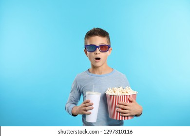 Emotional boy with 3D glasses, popcorn and beverage during cinema show on color background