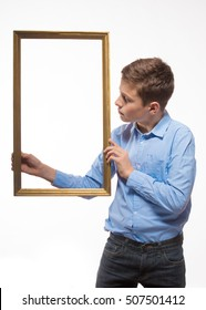 Emotional boy brunette in a blue shirt with a picture frame in the hands on a white background