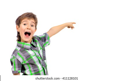 Emotional boy is pointing in the direction. Copy space. Education. Studio shot. Isolated over white.