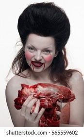 emotional brunette actress in the role of a vampire with blood drops on his face and a piece of bloody meat. woman in a transparent lace dress and lush hair with white feathers on a white background.