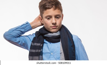Emotional brunette boy in a cap and scarf on a white background