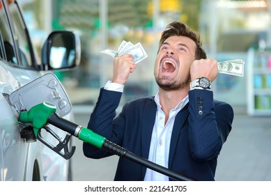 Emotional businessman counting money with gasoline refueling car at fuel station