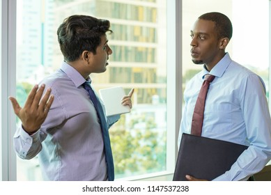 Emotional businessman talking about problems with coworker. Young entrepreneur spreading arms in despair when telling news to colleague. Serious conversation