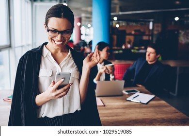 Emotional businesswoman in formal wear celebrating success on financial exchange reading latest news on smartphone, prosperous female ceo happy about achievement of company checking mail on telephone
