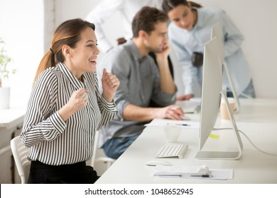 Emotional businesswoman looking at desktop monitor waiting in tension for online result, excited woman office employee clenching fists feeling enthusiastic cheering supporting, hope for win concept