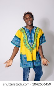 emotional cheerful African young man in national clothes-dashiki. posing on a white background in jeans. creative hair style for African hair, healthy teeth and smile. actively gesticulates hands