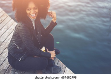 Emotional cheerful beautiful afro american woman with curly hair enjoying leisure time while looking away sitting against water.Positive pretty hipster girl recreating outdoors with good mood