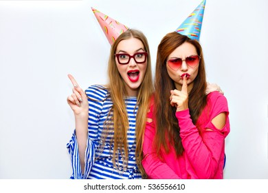 Emotional cheerful happy friends making grimace, smiling, showing silence sign. Cute attractive girls having great time together. Birhday party, fun, emotions. Isolated background. Place for text.