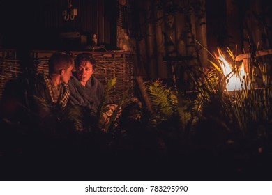 Emotional conversation between mother and mature teenager son around the campfire at night in countryside