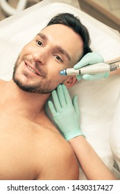 Emotional dark haired man smiling while cosmetologist in rubber gloves touching his face during the nourishing procedure