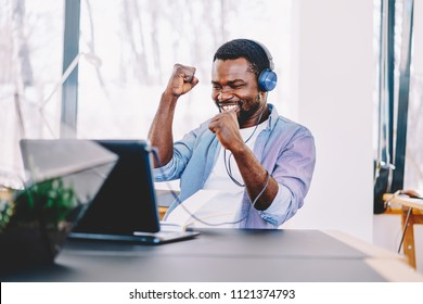 Emotional dark skinned male freelancer celebrating completed project successfully, happy african american football fan cheering for match watching online video on netbook and in headphones in coworkin