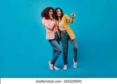 Emotional dark-haired ladies in jeans standing on blue background. Indoor photo of two surprised girls.