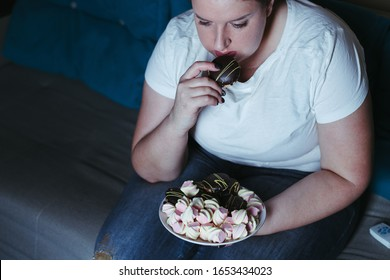 Emotional eating, mental disorder, depression, loneliness, stress. Lonely woman eating sweets and watching tv late in the night. Nerve food