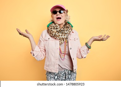 emotional excited old woman with raised arms greeting guests, singing songs.welcome. isolated yellow background. studio shot. gest. body language