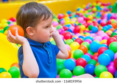 An emotional face of smiling baby playing in the balls pool. Happy kid playing with colored balls. Child playing with colorful balls in playground ball pool