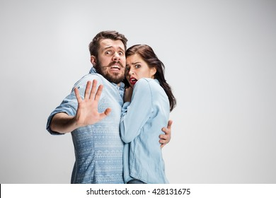 Emotional facial expression wide eyed couple, woman an man looking surprised open mouth on gray