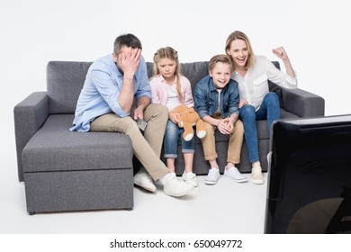 emotional family sitting on sofa and watching tv together
