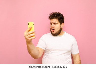 Emotional fat young man in white t-shirt is using smartphone on pink background, with shocked face looking into camera. Funny full man communicates on video call with surprised face.