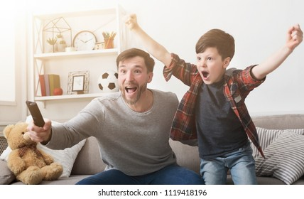 Emotional father and son watching football on TV and cheering favorite team at home