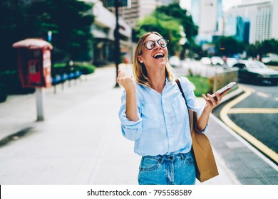 Emotional female feeling excited with getting great news holding smartphone and strolling on street, happy hipster girl screaming yes happy about success in competition online checking mail on phone