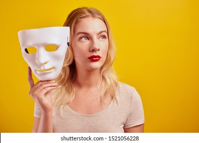 Emotional female person with white mask on yellow background. Internet fraud concept, anonymous, incognito, bipolar personality disorder, hypocrisy