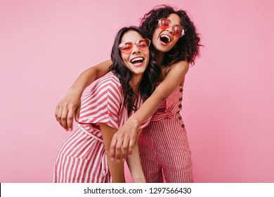 Emotional friends with beautiful tan, which emphasize light dresses, posing with sincere laugh on pink isolated background