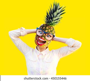 Emotional funny girl with pineapple instead head in fun sunglasses glasses. Summer funny pineapple with red lips and comic excited teeth smile laugh tongue on yellow. Vacation and travel concept.